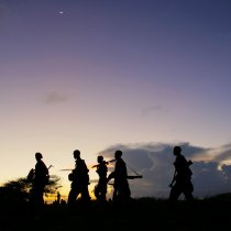 Soldiers of the Somali National Army (SNA) walk at dusk under a rising crescent moon near the outskirts of Afgooye, a town to the west of Somali capital Mogadishu. Photo: Flickr/UN Photo/Stuart Price.